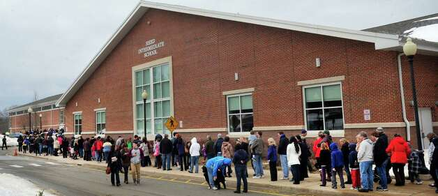 Parents and children from Newtown wait outside Reed Intermediate School in Newtown, Conn. for a give away of donated goods from the Sandy Hook Elementary School tragedy Sunday, Feb. 24, 2013. Photo: Michael Duffy / The News-Times