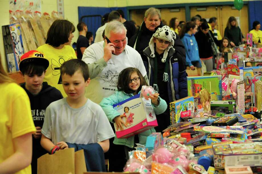 An excited Grace Hermes, 7, center, sees a toy she likes as parents and children from Newtown enter Reed Intermediate School in Newtown, Conn. and choose items during a give away of donated goods from the Sandy Hook Elementary School tragedy Sunday, Feb. 24, 2013. Photo: Michael Duffy / The News-Times