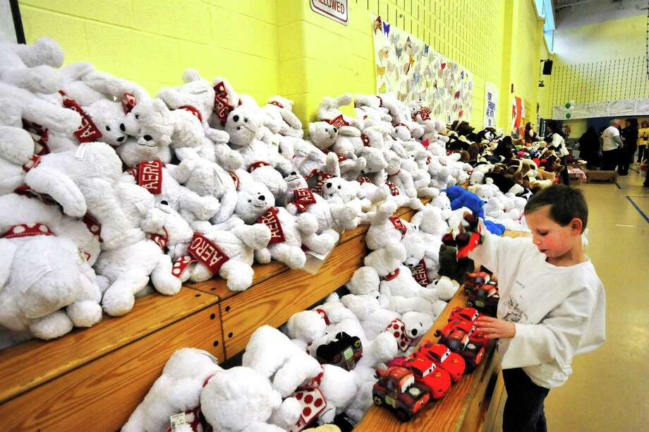 Caston Szilagyi, 7, chooses a toy he likes as parents and children from Newtown enter Reed Intermediate School in Newtown, Conn. and choose items during a give away of donated goods from the Sandy Hook Elementary School tragedy Sunday, Feb. 24, 2013. Photo: Michael Duffy / The News-Times