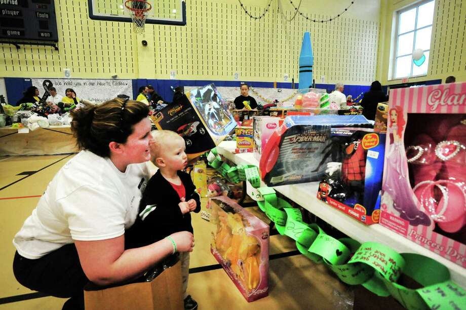 Becky Trosan and her son, Nicholas Laughlin, 1, look over a toys as parents and children from Newtown enter Reed Intermediate School in Newtown, Conn. and choose items during a give away of donated goods from the Sandy Hook Elementary School tragedy Sunday, Feb. 24, 2013. Photo: Michael Duffy / The News-Times