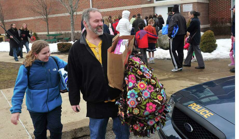 Samantha Black, 11, and her dad, Jeff, leave with their choices past parents and children from Newtown waiting outside Reed Intermediate School in Newtown, Conn. for a give away of donated goods from the Sandy Hook Elementary School tragedy Sunday, Feb. 24, 2013. Photo: Michael Duffy / The News-Times