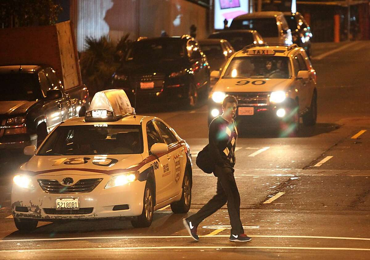 Taxis pass on Polk St. at Broadway streets in San Francisco, Calif., on Friday, February 22, 2013.