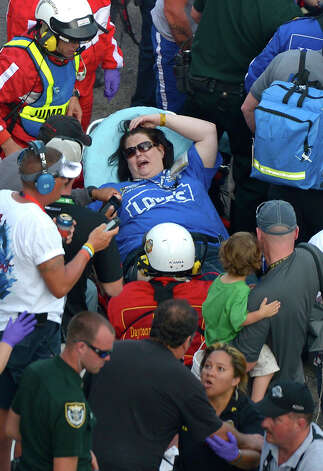 A spectator, center, is transported from the grandstands by emergency personnel after Kyle Larson's car hit the safety wall and fence along the front stretch on the final lap of the NASCAR Nationwide Series auto race at Daytona International Speedway in Daytona Beach, Fla., Saturday, Feb. 23, 2013. Several fans were injured when large chunks of debris flew into the grandstands. Photo: Phelan M. Ebenhack
