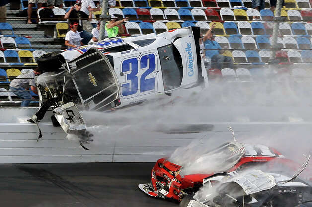 Kyle Larson (32) goes airborne and into the catch fence during a multi-car crash involving Justin Allgaier (31), Brian Scott (2) and others during the final lap of the NASCAR Nationwide Series auto race at Daytona International Speedway, Saturday, Feb. 23, 2013, in Daytona Beach, Fla.  Larson's crash sent car parts and other debris flying into the stands injuring spectators. Photo: John Raoux