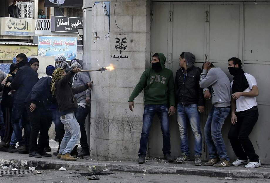 Palestinian men protesting the death of a young father take cover during a fight with Israeli troops in Hebron. Photo: Nasser Shiyoukhi, Associated Press