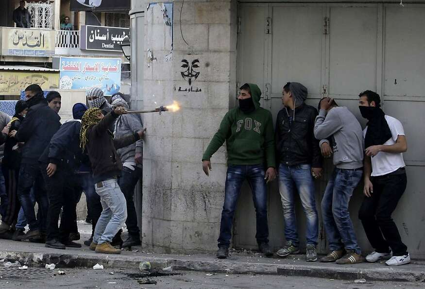 Palestinian men protesting the death of a young father take cover during a fight with Israeli troops