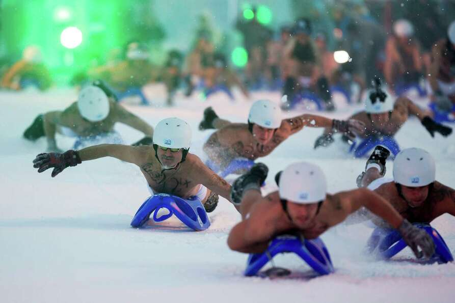 Competitors wearing only underwear and panties ride a sled in the 2013 naked snow-sledding competi