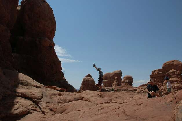 A hike does a handstand on the red rock trail at Arches National Park. Photo: San Antonio Express-News