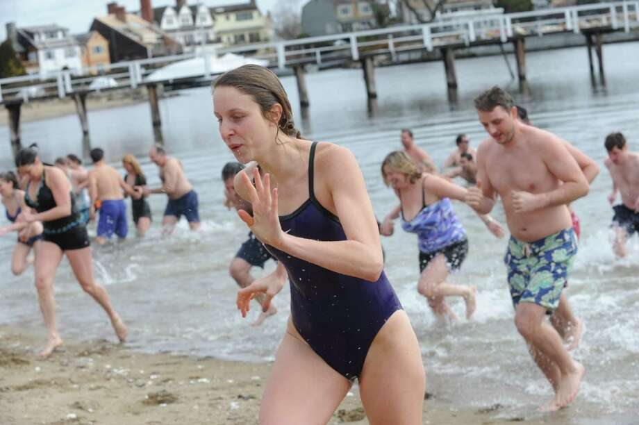 A guest runs out of the water at Family Centers of Greenwich's second annual Polar Bear Plunge in the Long Island Sound at Geneve Holdings, in Stamford, Conn., Sunday, Feb. 24, 2013, to benefit The Den for Grieving Kids, a Family Centers program. Photo: Helen Neafsey / Greenwich Time