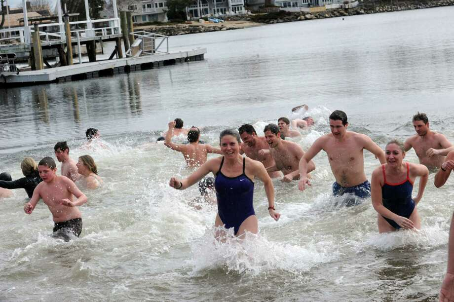 Guests run out of the water at Family Centers of Greenwich second annual Polar Bear Plunge in the Long Island Sound at Geneve Holdings, in Stamford, Conn., Sunday, Feb. 24, 2012, to benefit The Den for Grieving Kids, a Family Centers program. Photo: Helen Neafsey / Greenwich Time