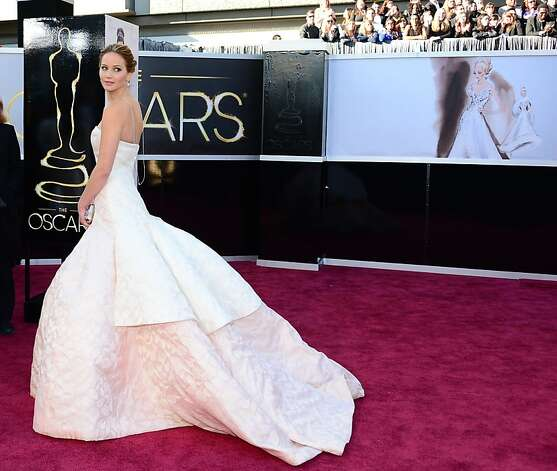 At left: Jennifer Lawrence looked like a bride in her swoosh of creamy train. Above: 9-year-old Quvenzhané Wallis in a puff-sleeve cobalt frock, with Halle Berry in glittery striped Versace. Photo: Frederic J. Brown, AFP/Getty Images