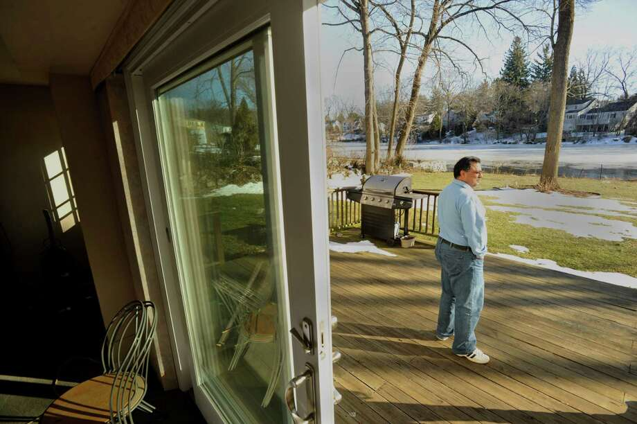 Sanjiv Puri stands on his back porch overlooking Cooper's Pond in Stamford on Monday, Feb. 18, 2013. Photo: Jason Rearick / The News-Times