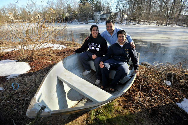 Deepali, Sanjiv and Manav pose in their row boat on the shore of Cooper's Pond on Monday, Feb. 18, 2013. Sanjiv taught his children to row. Manav uses rowing as a muscle-building exercise. Photo: Jason Rearick / The News-Times