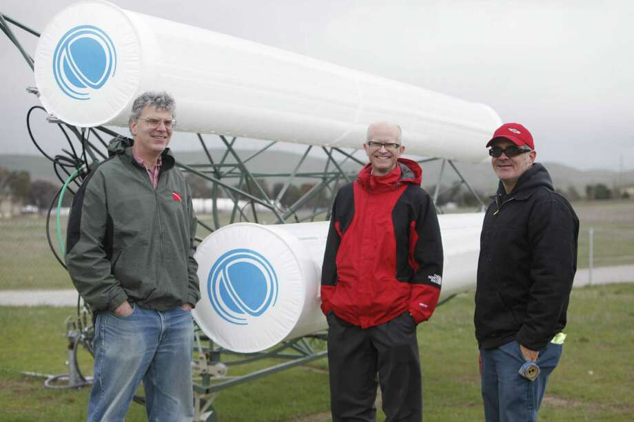 Cool Earth Solar and Sandia Laboratories staffers stand next to a couple of Cool Earth's solar tubes. Photo: Lea Suzuki / San Francisco Chronicle