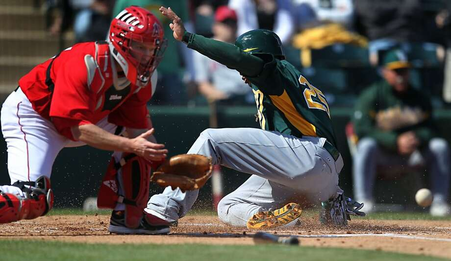 Oakland Athletics Chris Young slides safely into home plate ahead of the throw to Los Angeles Angels catcher Luke Carlin during their spring training exhibition baseball game Sunday, Feb. 24, 2013, in Tempe, Ariz. Photo: Lance Iversen, The Chronicle