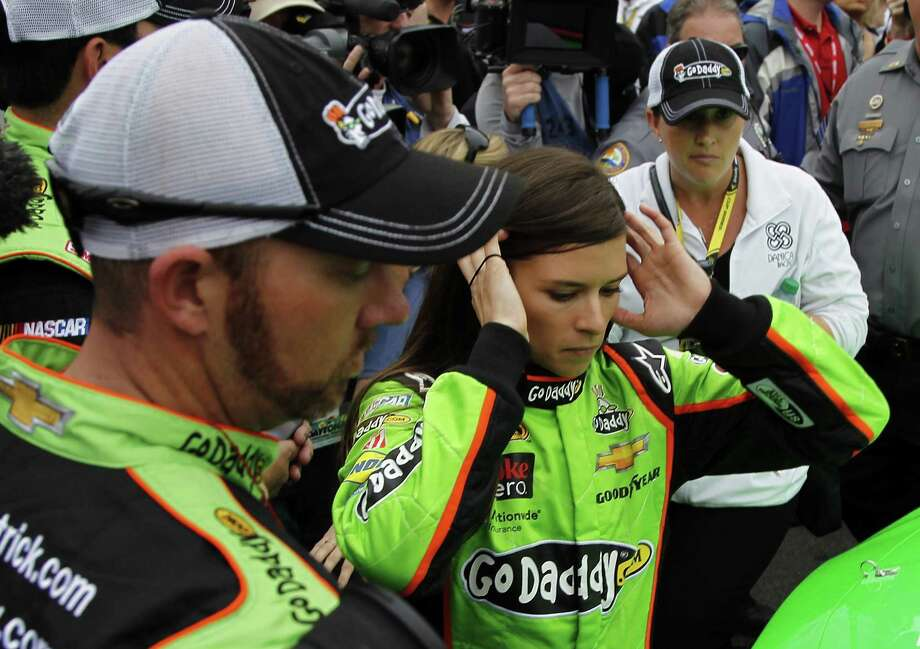 Danica Patrick, center, prepares to get in her car before the start of the NASCAR Daytona 500 Sprint Cup Series auto race at Daytona International Speedway, Sunday, Feb. 24, 2013, in Daytona Beach, Fla. (AP Photo/Terry Renna) Photo: Terry Renna