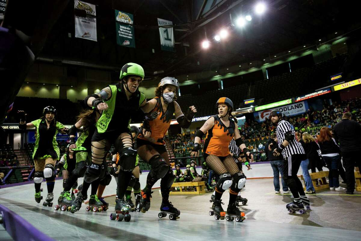 The Saint Hellions, in orange, and the Sugar Skulls, in green, go head-to-head at the season opener of the Banked Track Roller Derby, presented by the Tilted Thunder Rail Birds, on Sunday, Feb. 24, 2013, at Comcast Arena in Everett, Wash.