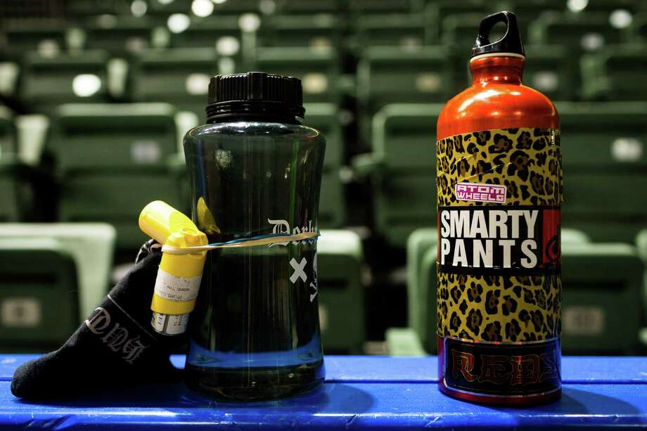 Players' water bottles, adorned with stickers and an asthma nebulizer, sit on the side of the rink at the season opener of the Banked Track Roller Derby, presented by the Tilted Thunder Rail Birds, on Sunday, Feb. 24, 2013, at Comcast Arena in Everett, Wash. Four teams - the Saint Hellions, the Sugar Skulls, the Rolling Blackouts and Royal Crush - went head-to-head for a win. Photo: JORDAN STEAD / SEATTLEPI.COM