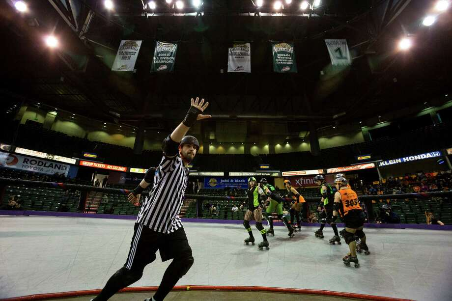 The Saint Hellions, in orange, and the Sugar Skulls, in green, go head-to-head at the season opener of the Banked Track Roller Derby, presented by the Tilted Thunder Rail Birds, on Sunday, Feb. 24, 2013, at Comcast Arena in Everett, Wash. Photo: JORDAN STEAD / SEATTLEPI.COM