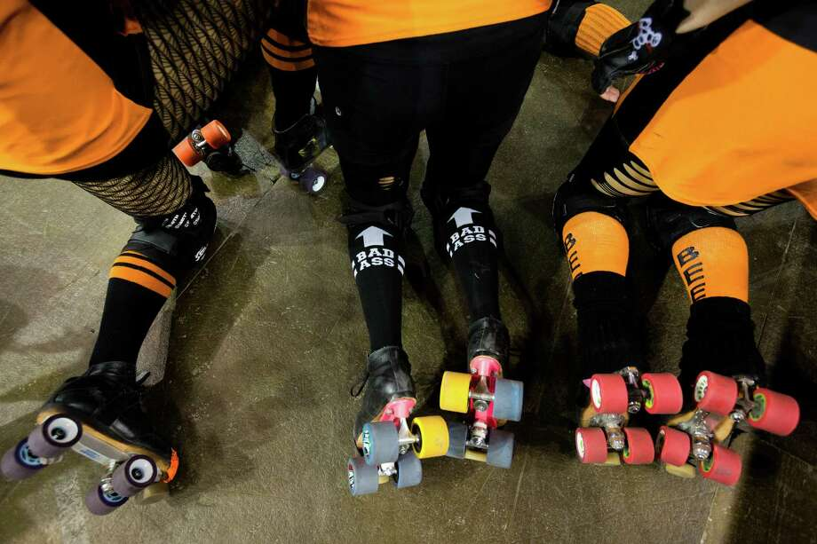 Players on the Saint Hellions team kneel while listening to their captain at the season opener of the Banked Track Roller Derby, presented by the Tilted Thunder Rail Birds, on Sunday, Feb. 24, 2013, at Comcast Arena in Everett, Wash. Four teams - the Saint Hellions, the Sugar Skulls,
