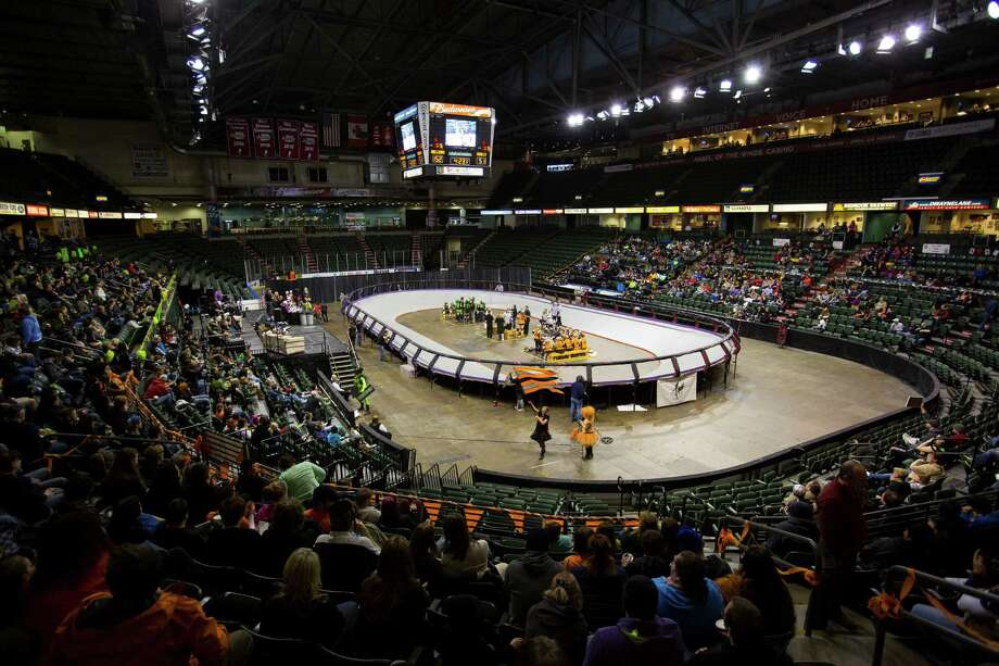 Crowds watch the Saint Hellions, in orange, and the Sugar Skulls, in green, go head-to-head at the season opener of the Banked Track Roller Derby, presented by the Tilted Thunder Rail Birds, on Sunday, Feb. 24, 2013, at Comcast Arena in Everett, Wash. Photo: JORDAN STEAD / SEATTLEPI.COM