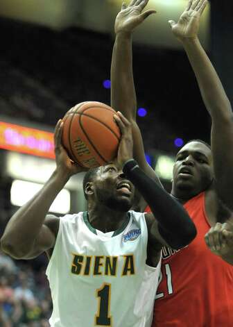 O.D. Anosike of Siena, left, puts up a shot over a Radford defender during their game at the Times Union Center on Sunday, Feb. 24, 2013 in Albany, NY.  (Paul Buckowski / Times Union) Photo: Paul Buckowski  / 00021251A