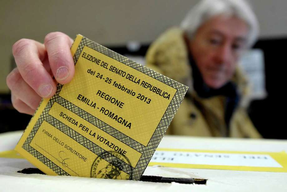 A man casts his vote for the Italian Senate, in Piacenza, Italy, Sunday, Feb. 24, 2013. Italy votes in a watershed parliamentary election Sunday and Monday that could shape the future of one of Europe's biggest economies. (AP Photo/Marco Vasini) Photo: Marco Vasini, STR / AP