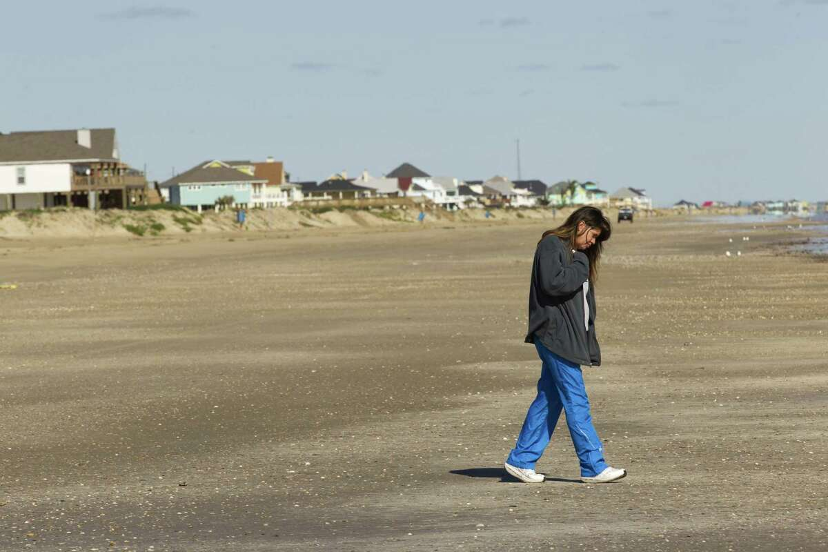 Christal Mears walks along the beach recently near a line of recently built homes in Crystal Beach. The Bolivar Peninsula is experiencing a comeback nearly five years after Hurricane Ike.