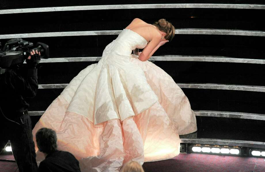 Actress Jennifer Lawrence stumbles as she walks on stage to accept the award for best actress in a leading role for Silver Linings Playbook during the Oscars at the Dolby Theatre on Sunday Feb. 24, 2013, in Los Angeles.  (Photo by Chris Pizzello/Invision/AP) Photo: Chris Pizzello, Associated Press / Invision