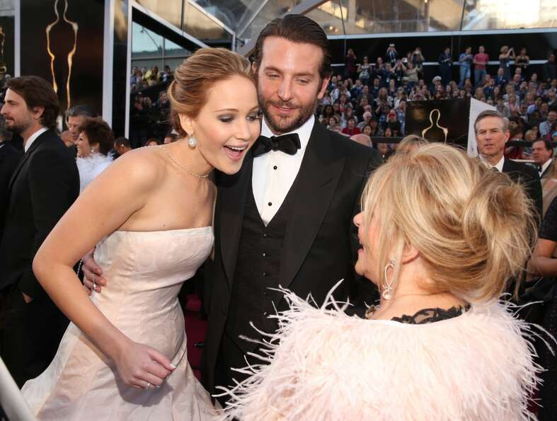 Actors Jennifer Lawrence, Bradley Cooper, and Jacki Weaver arrive at the Oscars held at Hollywood &