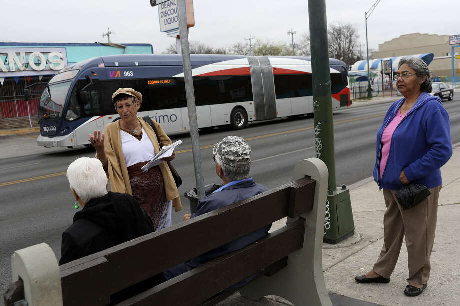 Celia Longoria asks bus riders on Fredericksburg Road to sign a petition for VIA Metropolitan Transit to bring back the 91 and 92 routes, which ended with the start of Prímo rapid transit, as one of the new buses passes by. Photo: Lisa Krantz / San Antonio Express-News