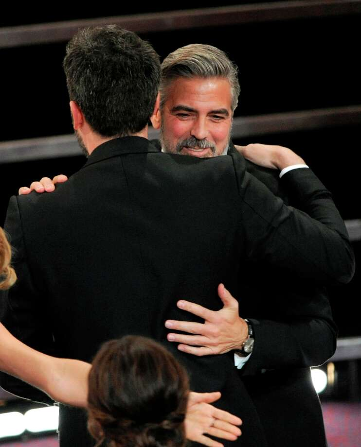 Ben Affleck, left, hugs George Clooney after Argo is announced the winner for the award for best picture during the Oscars at the Dolby Theatre on Sunday Feb. 24, 2013, in Los Angeles.  (Photo by Chris Pizzello/Invision/AP) Photo: Chris Pizzello, Associated Press / Invision