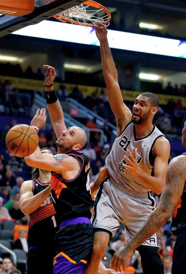 The Spurs' Tim Duncan dunks over the Suns' Marcin Gortat during the first half  Sunday, Feb. 24, 2013, in Phoenix. Photo: Matt York, Associated Press / AP
