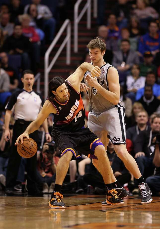 Luis Scola #14 of the Suns handles the ball under pressure from Tiago Splitter #22 of the Spurs during the first half at US Airways Center on Feb. 24, 2013. Photo: Christian Petersen, Getty Images / 2013 Getty Images