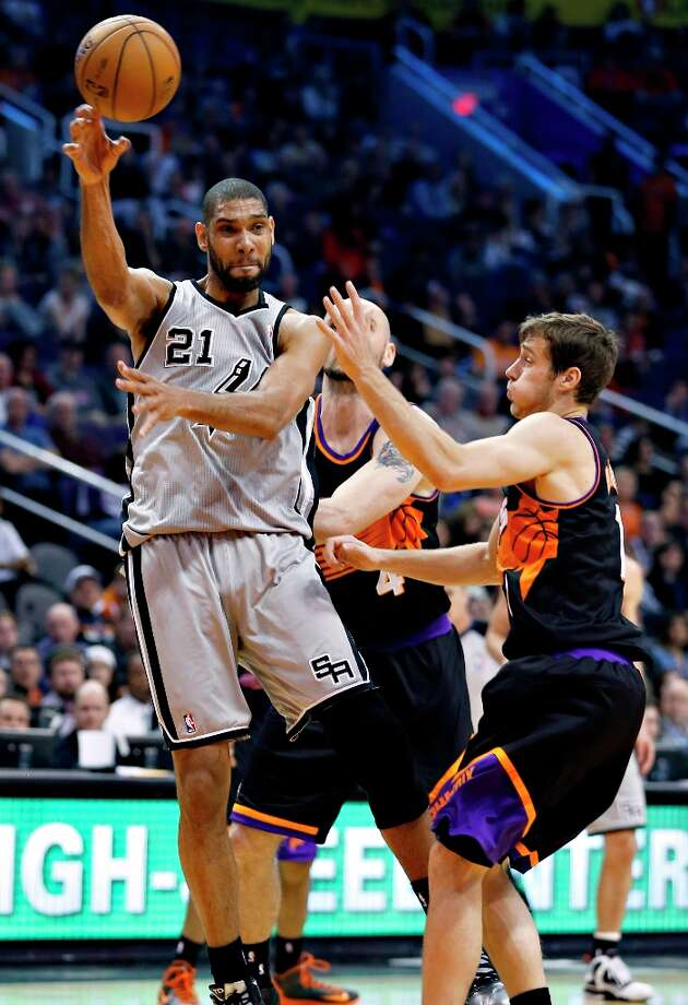 The Spurs' Tim Duncan (21) passes under pressure from the Suns' Goran Dragic during the first half  Sunday, Feb. 24, 2013, in Phoenix. Photo: Matt York, Associated Press / AP