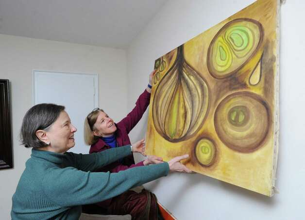 At left, Zdena Heller, gets help hanging one of her paintings from Emily Cox, a home-care helper provided through At Home in Greenwich, in Heller's Greenwich home, Friday afternoon, Feb. 15, 2013. Zdena's husband Gilbert has Parkinson's disease and both he and his wife receive assistance from helpers provided through At Home Greenwich, a nonprofit, nonsectarian organization founded to help senior residents of Greenwich get access to life services and to a network of social connections and events. Photo: Bob Luckey / Greenwich Time