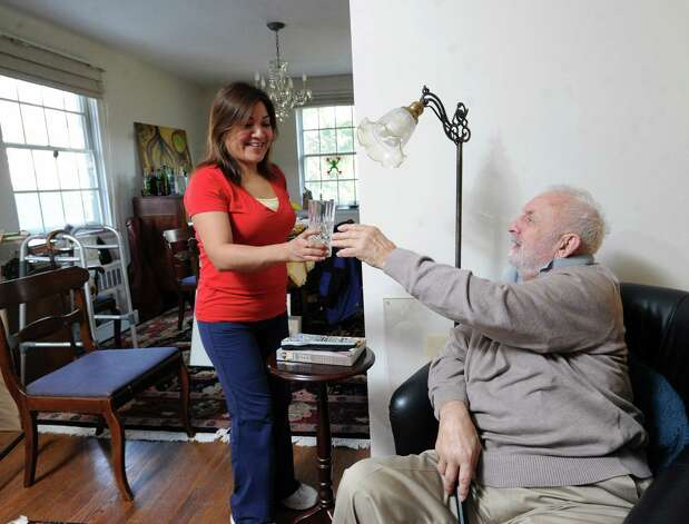 At left, Gladys Castaneda, a home-care helper provided through At Home in Greenwich, gives a glass of water to Gilbert Heller in Heller's Greenwich home, Friday afternoon, Feb. 15, 2013. Gilbert has Parkinson's disease and both he and his wife receive assistance through helpers provided through At Home Greenwich, a nonprofit, nonsectarian organization founded to help senior residents of Greenwich get access to life services and to a network of social connections and events. Photo: Bob Luckey / Greenwich Time