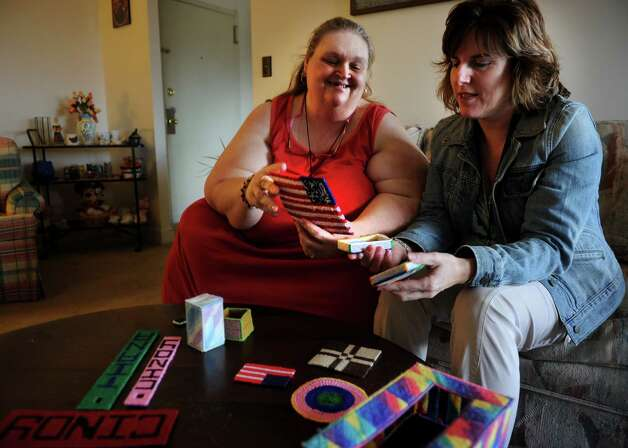 Cindy Hall, left, shares some of her new needlepoint projects with Cara Ruddy, her transition coordinator, at her apartment on Huntington Turnpike in Bridgeport on Thursday, January 31, 2013. Hall transitioned to the apartment from a nursing home fifteen months ago. Photo: Brian A. Pounds