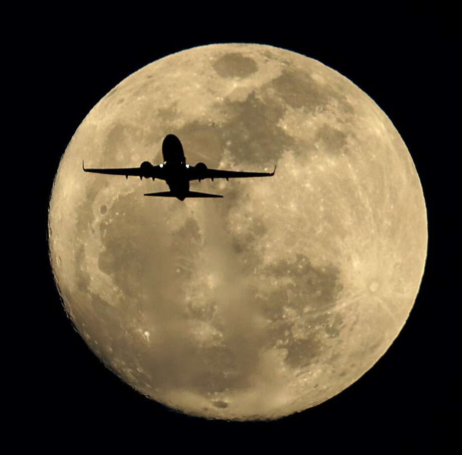 Southwest, now with daily flights to the Sea of Tranquility: A Southwest Airlines jet is silhouetted against the full moon over Sky Harbor Airport in Phoenix. Photo: Charlie Riedel, Associated Press