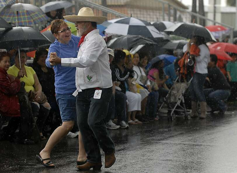 A couple does a a traditional Mexican dance in the rain at the annual Charro Days Festival on Sunday
