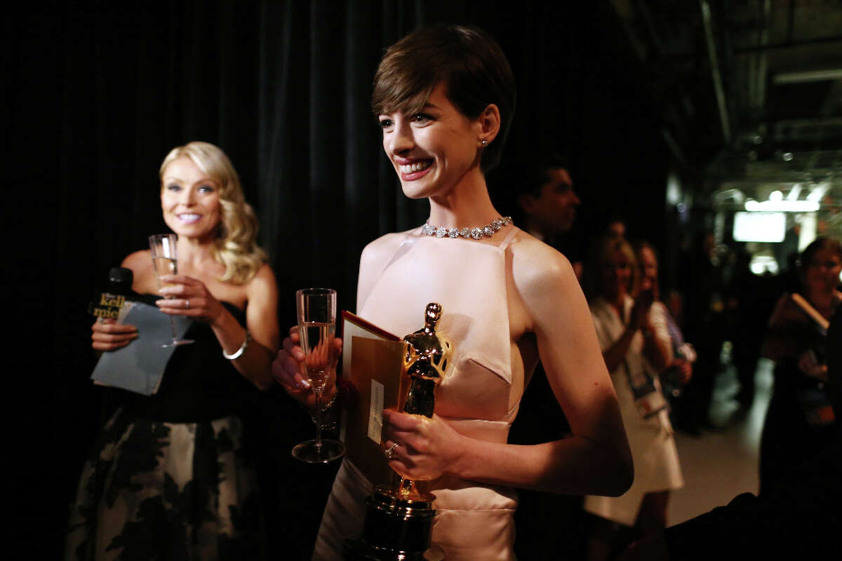 Actress Anne Hathaway speaks with tv personality Kelly Ripa backstage following her win for the Best Actress in a Supporting Role during the Oscars held at the Dolby Theatre on February 24, 2013 in Hollywood, California.