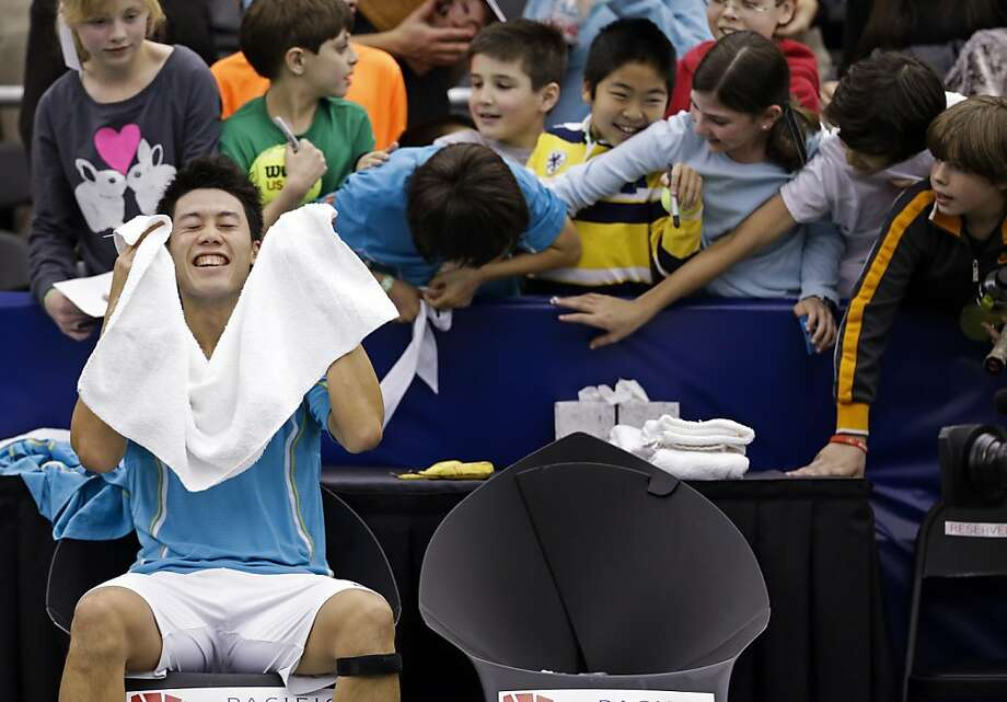 Kei Nishikori, of Japan, celebrates as fans reach for souvenirs after Nishikori defeated Feliciano Lopez, of Spain, in the final round match at the U.S. National Indoor Championships tennis tournament, Sunday, Feb. 24, 2013, in Memphis, Tenn. Nishikori won 6-2, 6-3.  Photo: Mark Humphrey, Associated Press