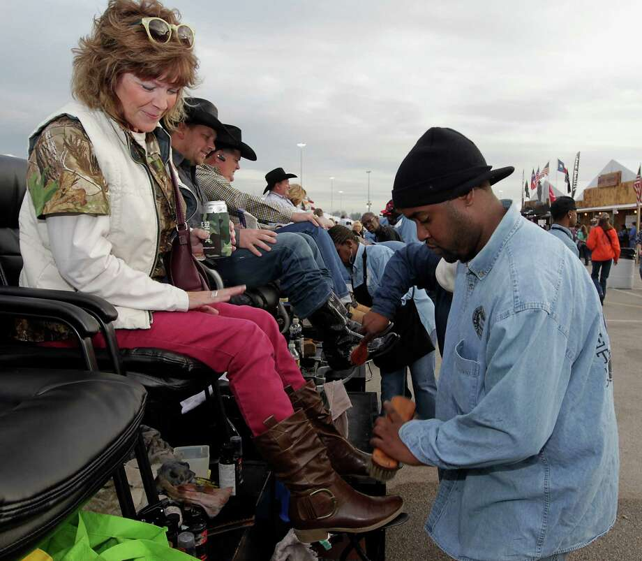 Tina Kutach left, has her boots shined by James Harris during the Houston Livestock Show and Rodeo WorldâÄôs Championship Bar-B-Que Contest at Reliant Park Friday, Feb. 22, 2013, in Houston. Photo: James Nielsen, Houston Chronicle / © 2013  Houston Chronicle