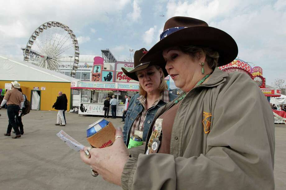 Laurie Madden left, and Elyse Turla right, look over a map during the Houston Livestock Show and Rodeo World's Championship Bar-B-Que Contest at Reliant Park Friday, Feb. 22, 2013, in Houston. Photo: James Nielsen, Houston Chronicle / © 2013  Houston Chronicle