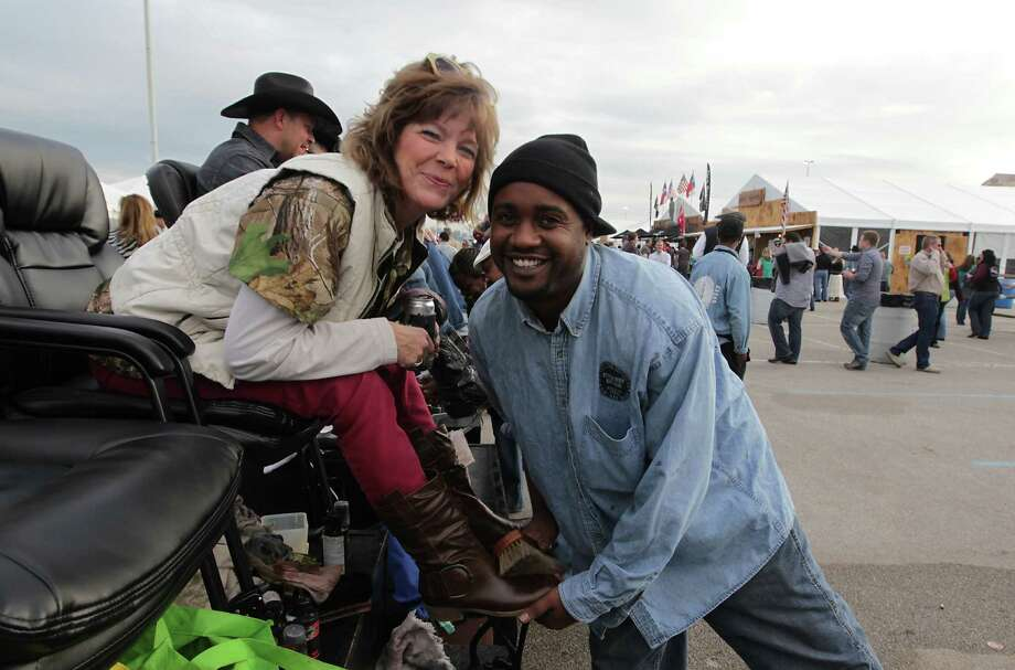 Tina Kutach left, poses for a photograph with James Harris, after Harris shined her boots during the Houston Livestock Show and Rodeo WorldâÄôs Championship Bar-B-Que Contest at Reliant Park Friday, Feb. 22, 2013, in Houston. Photo: James Nielsen, Houston Chronicle / © 2013  Houston Chronicle
