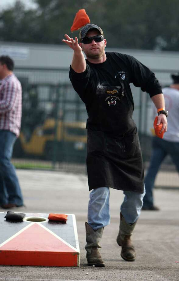 Chris Jackson throws a sand bag while playing a game of corn hole during the Houston Livestock Show and Rodeo WorldâÄôs Championship Bar-B-Que Contest at Reliant Park Friday, Feb. 22, 2013, in Houston. Photo: James Nielsen, Houston Chronicle / © 2013  Houston Chronicle