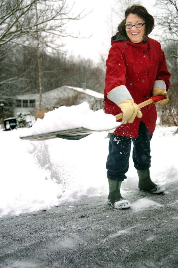 Nancy Arruzza shovels her Ansonia driveway Thursday morning. Photo: Autumn Driscoll / Connecticut Post
