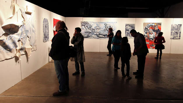 "People look at art by Francisco Delgado part of the ""Queering History: A Retrospective of Damage"" at 107 Gallery during Second Saturday in the South Flores Arts District Saturday Feb. 9, 2013. Photo: Edward A. Ornelas, San Antonio Express-News / © 2013 San Antonio Express-News"