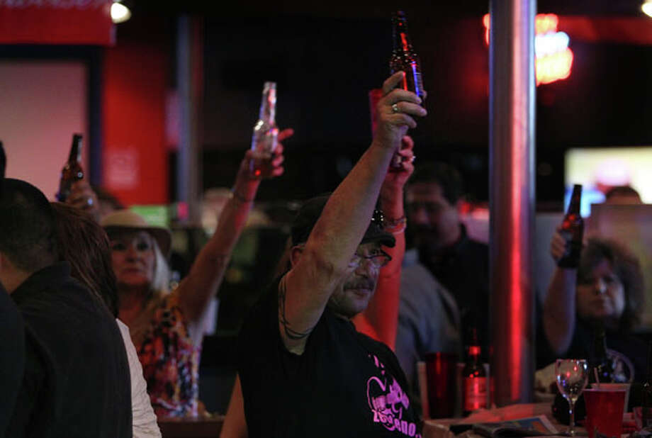 Friends and fans raise their drinks in honor of Norma Zenteno during the Benefit and Tribute Concert at SRO's Sports Bar & Cafe on Sunday, Feb. 24, 2013, in Houston.  Norma Zenteno lost her battle with breast cancer on Friday. Photo: Mayra Beltran, Houston Chronicle / © 2013 Houston Chronicle
