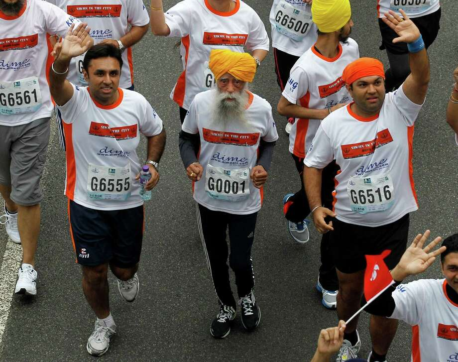 Centenarian marathon runner Fauja Singh, 101, center, originally from Beas Pind, in Jalandhar, India but who now lives in London, runs in a 10-kilometer race, part of the annual Hong Kong Marathon, in Hong Kong Sunday, Feb. 24, 2013. Singh will retire from public racing after competing in the marathon. Photo: Kin Cheung, AP / AP